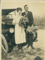 John Hayes White and his wife standing in front of a car. Both are carrying flowers.