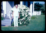 An unidentified woman standing in front of a flowering bush.